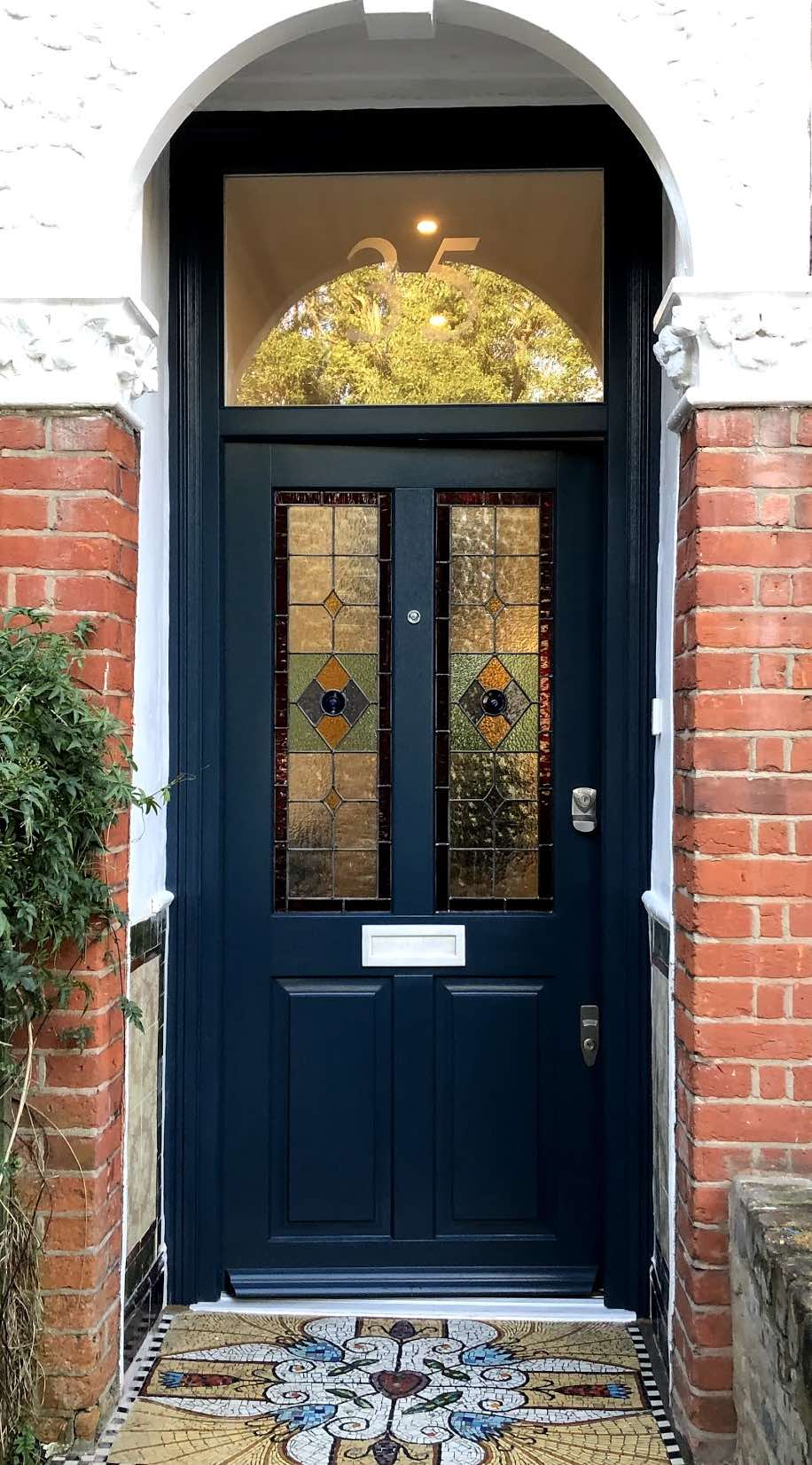 Wooden front door painted in Farrow and Ball Hague Blue