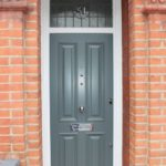 wooden front door grey colour white frame and red brick wall