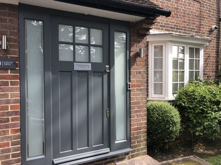 wooden front door with glass fitted at the entrance of a red brick house